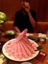 Then, thin slices of beef are place on the table. Each person grabs a slice of meat with their chopsticks and swishes it around in the broth (it makes the sound shabu-shabu) for a few seconds until it cooks. Then eat! Note the marbling in the beef.